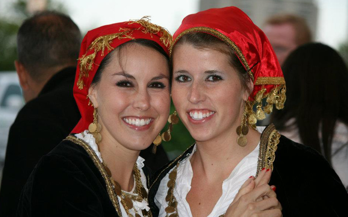 """<span  class=""""uc_style_uc_tiles_grid_image_elementor_uc_items_attribute_title"""" style=""""color:#ffffff;"""">Sisters take a break from dancing and enjoy a fun moment at the Tulsa Greek Festival</span>"""